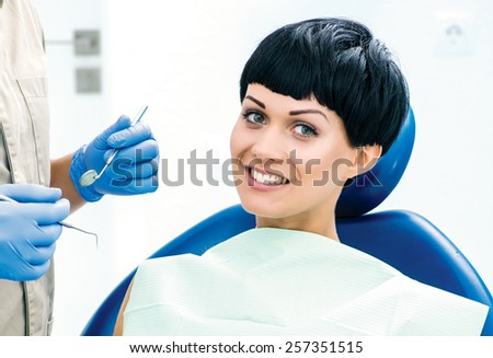 Waiting for the dentist. Dentist makes the process of treatment of a beautiful young girl. - stock photo