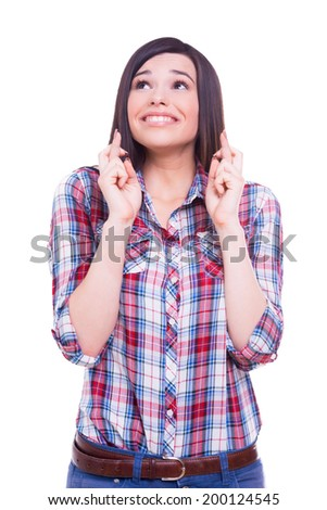 Waiting for the moment. Beautiful young woman keeping fingers crossed while standing isolated on white - stock photo