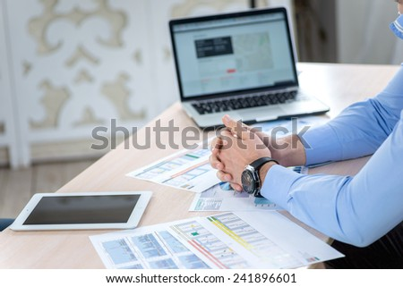 Waiting for work. Serious businessman sitting at the negotiating table in the office and put his hands on the table close-up view of hands. Business people dressed in formal wear - stock photo