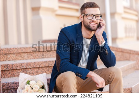 Waiting for you! Handsome young man in smart jacket talking on the mobile phone and smiling while sitting on the staircase with bouquet of roses laying near him - stock photo