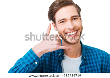 Waiting for your call. Confident young man gesturing mobile phone near his face and smiling while standing against white background - stock photo