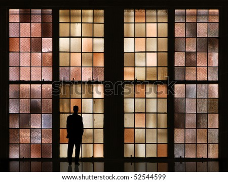 waiting man in front of colorful windows - stock photo