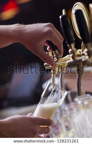 waiting man pouring beer into the glass - stock photo