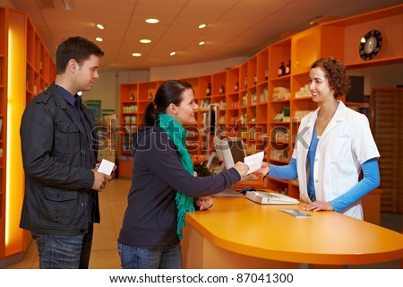 Waiting queue with customers in a pharmacy with pharmacist - stock photo
