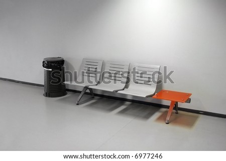 Waiting room - chairs, trash bin and an orange table - stock photo