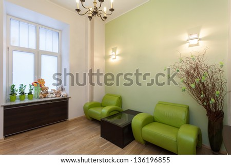 Waiting room with green furniture and toys - stock photo