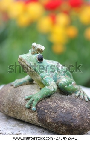 Waiting weathered stone frog statue waiting on a stone to be kissed in the garden, seen from front view. Character from a Russian fairytale. Black eyes. Blurry tulip flower garden background, green.