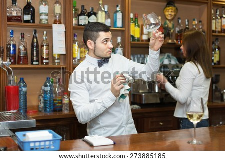 Waitress and barmen working in modern bar. Focus on man - stock photo