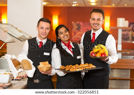 Waitress and waiters posing with food at buffet in restaurant - stock photo