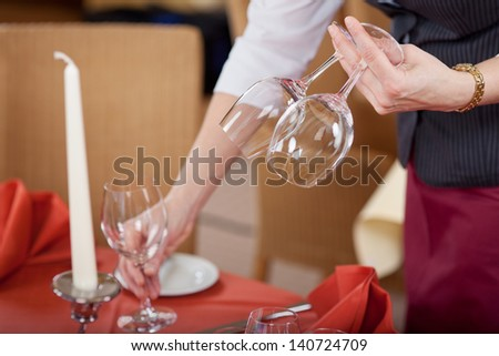 Waitress arranging wineglasses on table in restaurant - stock photo