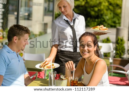 Waitress bring couple lunch food restaurant sunny terrace sandwiches - stock photo