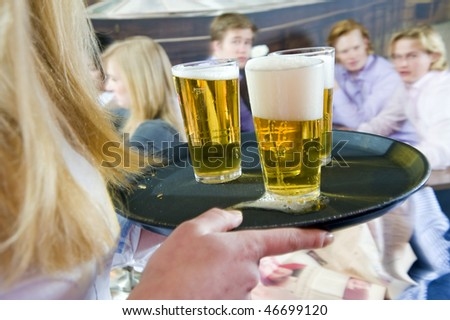 Waitress, bringing a round of beers to a waiting group of customers - stock photo