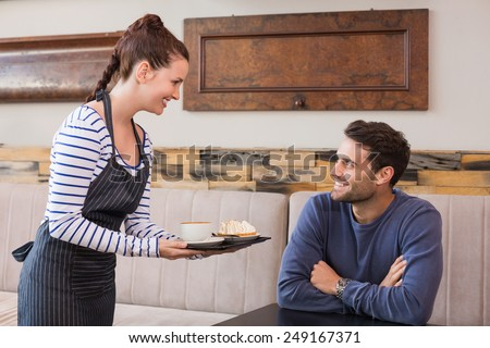 Waitress bringing man coffee and tart at the cafe - stock photo
