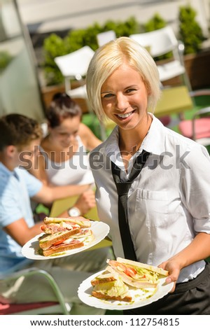 Waitress bringing sandwiches on plates fresh lunch restaurant terrace - stock photo