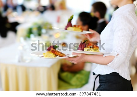 Waitress carrying three plates with meat dish on some festive event, party or wedding reception - stock photo