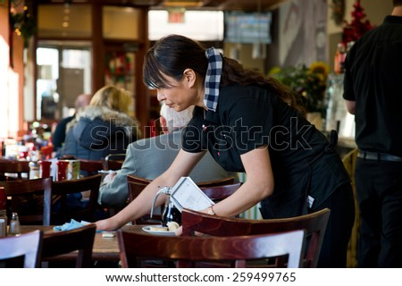 Waitress clearing table - stock photo