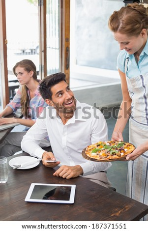 Waitress giving pizza to a smiling young man at the coffee shop - stock photo