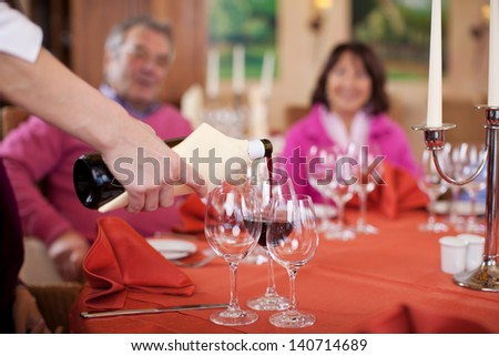 waitress�´hand pouring red wine at guest�´s glasses - stock photo