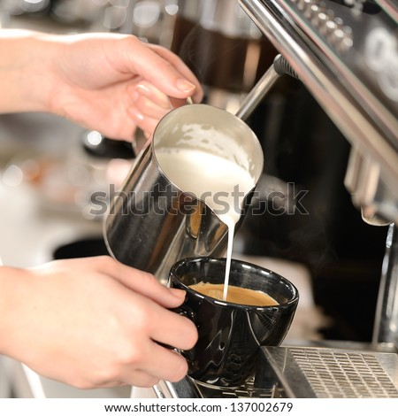 Waitress hands pouring milk making cappuccino - stock photo