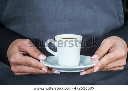 waitress holding cup of espresso coffee