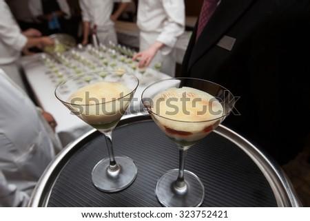 waitress holding tray dessert for dinner in hotel restaurant kitchen - stock photo