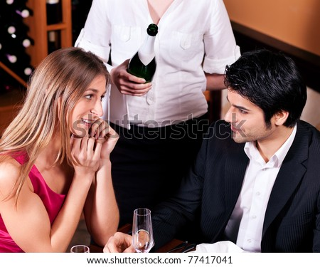 Waitress in a fancy restaurant filling glasses of couple with champagne - stock photo