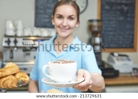 Waitress In Cafe Serving Customer With Coffee - stock photo