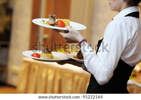 Waitress is carrying three plates with meat dish - stock photo