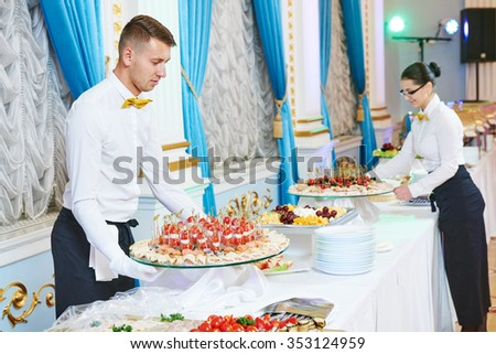 waitress occupation. Young woman with food on dishes servicing in restaurant during catering the event - stock photo