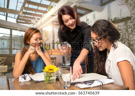 Waitress server helping client patron customer with menu order on sunny patio  - stock photo