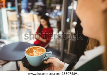 Waitress serving a cup of coffee in cafe - stock photo