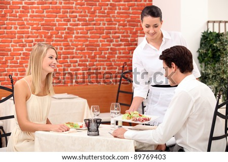 Waitress serving a young couple in a restaurant - stock photo