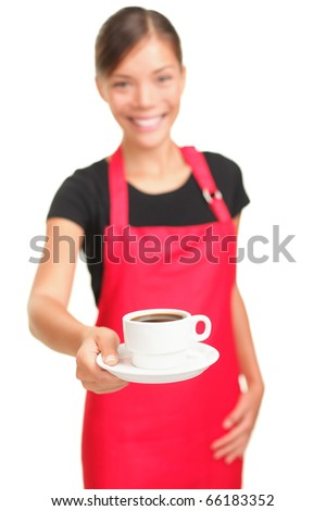 Waitress serving coffee. Barista cafe shop woman smiling showing cup of coffee. Isolated on white background. Focus on coffee. - stock photo