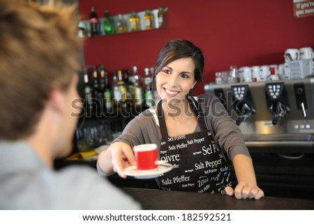 Waitress serving coffee from machine - stock photo