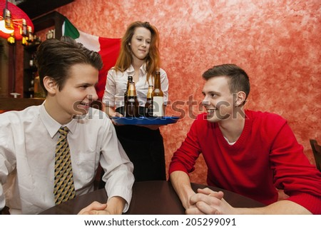 Waitress serving drinks to men in restaurant