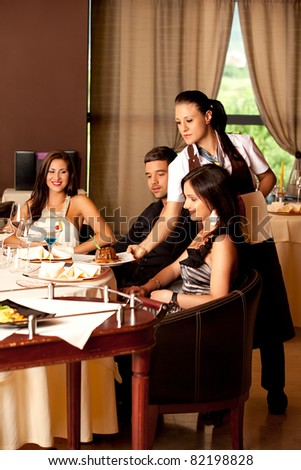 waitress serving food young people restaurat table - stock photo