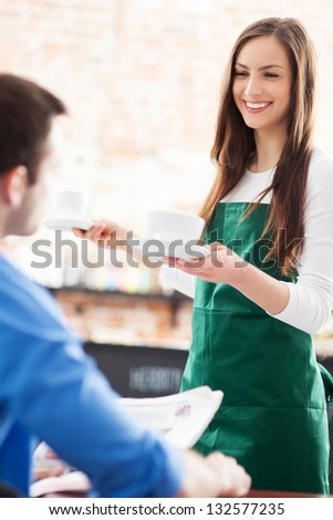 Waitress serving man at cafe - stock photo