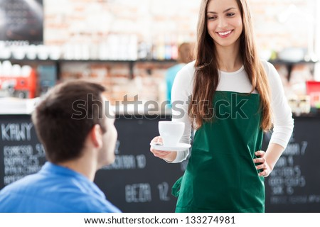 Waitress serving man coffee - stock photo