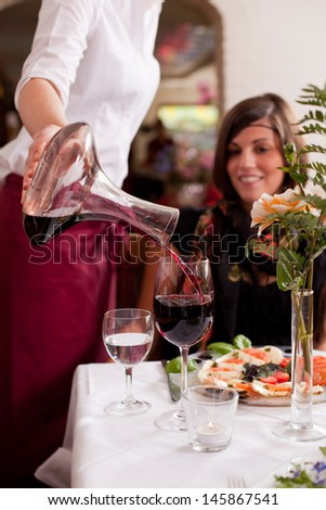 Waitress serving red wine in a restaurant watched by the customer seated at the dining table, closeup of the hands - stock photo
