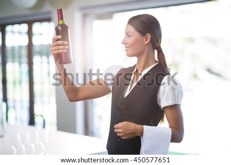 Waitress standing in restaurant checking a wine bottle