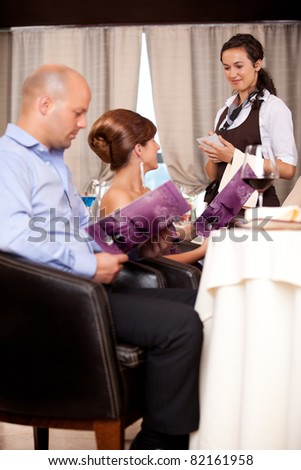 waitress taking meal order restaurant table young couple - stock photo