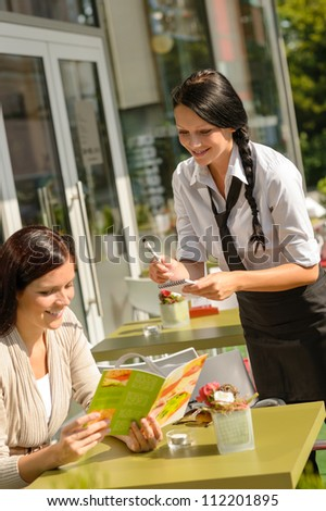 Waitress taking woman's order at cafe bar menu smiling sunny - stock photo