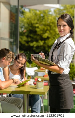 Waitress waiting for clients to decide cafe order restaurant terrace - stock photo