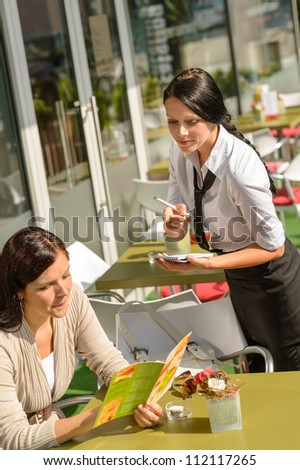 Waitress waiting for woman to order menu cafe bar deciding - stock photo
