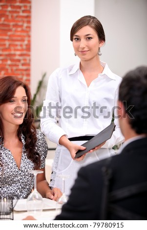 Waitress with a menu in a restaurant - stock photo
