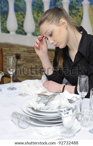 waitress wondered at the table with dirty dishes - stock photo