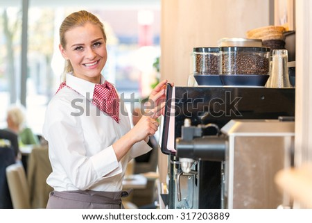 Waitress working at coffee machine in bakery, bistro or cafe