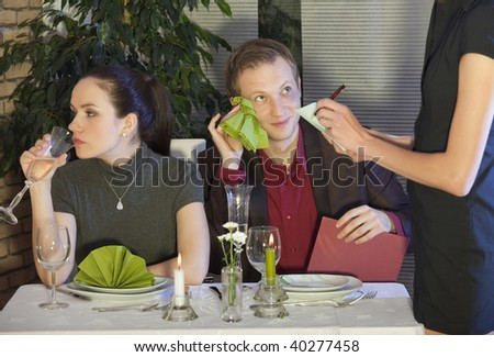 waitress writing a order from couple in restaurant - stock photo