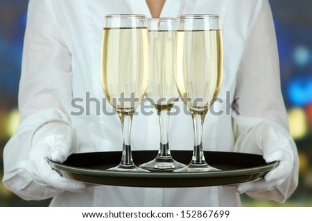 Waitresses holding tray with glasses of champagne - stock photo