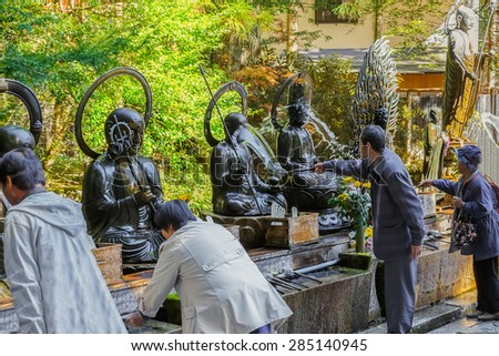 WAKAYAMA, JAPAN - OCTOBER 29: Okunoin Temple in Wakayama, Japan on October 29, 2014. Unidentified people bathing the Buddha in front of Okunoin Temple
